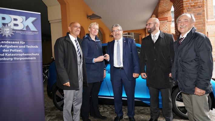 Innenminister Lorenz Caffier übergibt symbolisch die neuen Elektrofahrzeuge der Leiterin des Zentralen Fuhrparks der Landesregierung Nadine Kant.