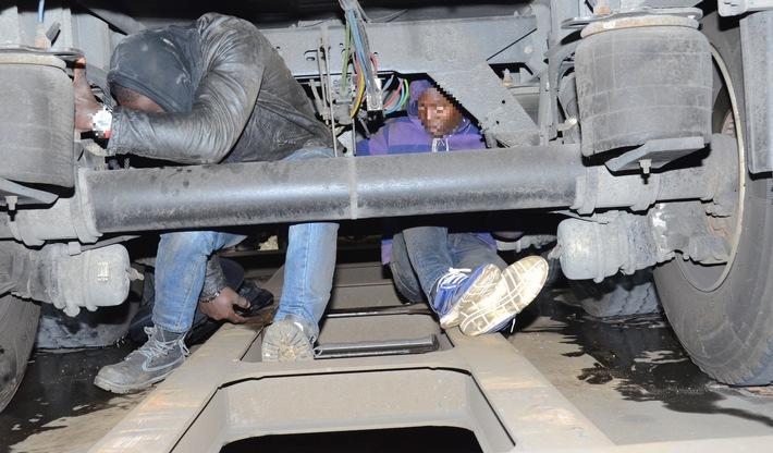 Migranten sitzen auf den schmalen Stahlstreben eines Güterzuges zwischen Rädern und Achsen eines Lkw-Aufliegers (Foto: Bundespolizei)