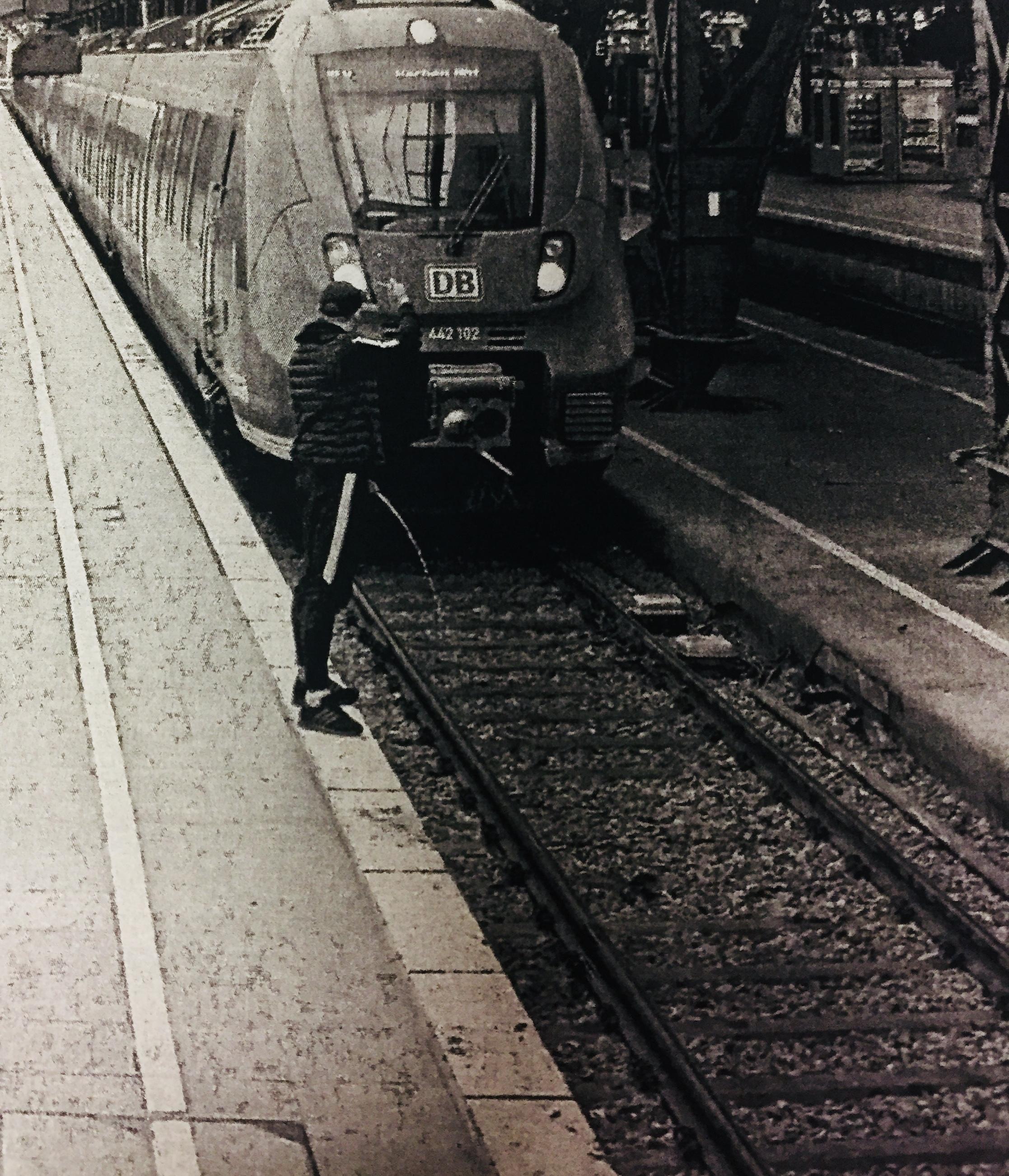 Mann uriniert vor einfahrende Bahn und zeigt Mittelfinger