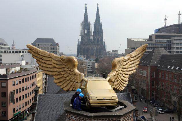 """Insgesamt zwölf Auszubildende der Ford-Werke reinigten und restaurierten in den vergangenen Wochen das Flügelauto des Künstlers HA Schult. Nachdem der """"Goldene Vogel"""" sicher auf dem Treppenturm des Kölnischen Stadtmuseums gelandet war, wurde er durch Spezialisten der Stadt Köln auf der erneuerten Betonplatte montiert. Die Verwendung dieses Bildes ist für redaktionelle Zwecke honorarfrei. Veröffentlichung bitte unter Quellenangabe: """"obs/Ford-Werke GmbH"""""""