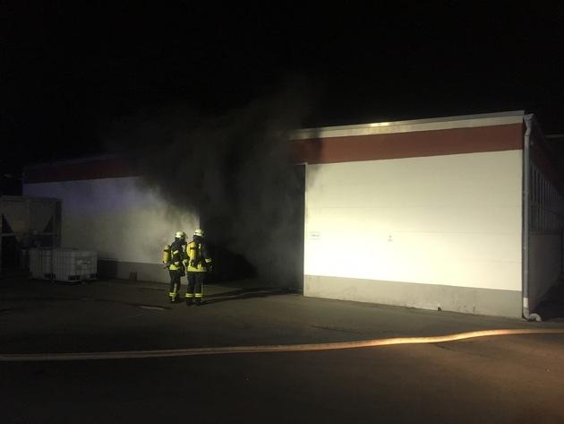 Nach dem Öffnen des Hallentores dringt dichter Brandrauch nach außen.