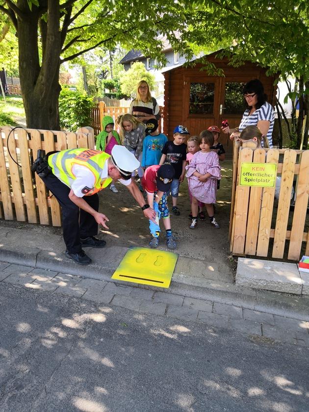 """Polizeikommissar Ralf Buchmeier (Verkehrssicherheitsberater der PI Goslar) sprüht zusammen mit den Kindern die """"Gelben Füße"""""""