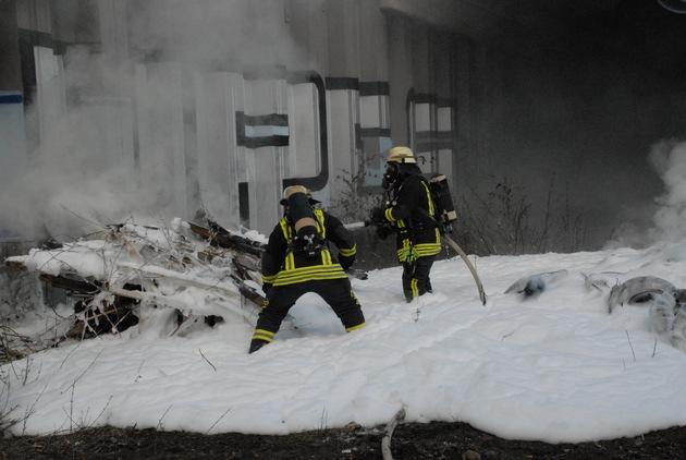 Die Brandschützer in dem Schaumteppich, der über die Autoreifen gelegt wurde