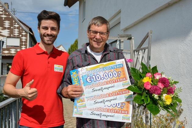 Drei Schecks, drei Mal 10.000 Euro: Postcode-Moderator Giuliano Lenz (links) hat Kurt aus Hohentengen persönlich überrascht. Foto: Postcode Lotterie/Wolfgang Wedel