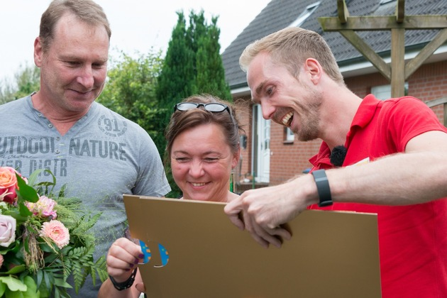Petra ist gespannt: Gleich erfährt sie, wie hoch die Gewinnsumme ist. Postcode-Moderator Felix Uhlig (rechts) ist ihr behilflich. Foto: Postcode Lotterie/Wolfgang Wedel