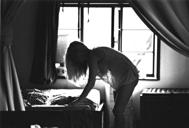 Schwarzweiß Fotografie: Frau über Bett gebeugt