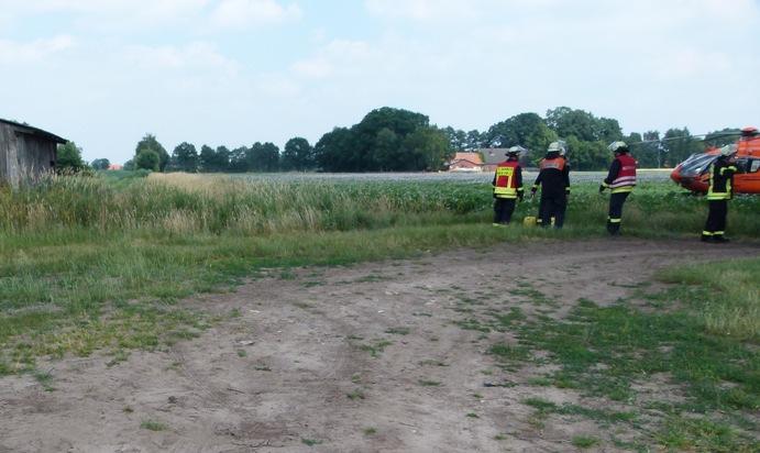 Der im Graben liegende Traktor wurde von dem hohen Gras verdeckt. Der Rettungshubschrauber landete rechts davon in unmittelbarer Nähe. Foto: Polizei Minden-Lübbecke
