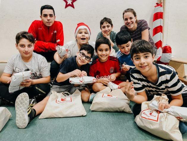 """Kinder des Projekts """"Fußball trifft Kultur"""" in Köln freuen sich über Geschenke von Kaufland, die sie nach einem gemeinsamen Spielenachmittag in der Schulturnhalle erhielten. Foto: Kaufland"""