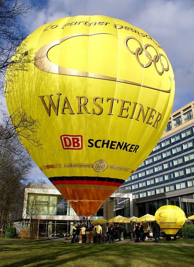 """WARSTEINER, Co-Sponsor der deutschen Olympiamannschaft und weltweiter Botschafter deutscher Bierkultur, lässt zum ersten Mal jenen Heißluftballon steigen, der die deutsche Fan-Fahne auf dem Luftweg in die Olympia-Stadt Beijing bringen wird. Mit im Ballonkorb: Jene schwarz-rot-goldene Fan-Fahne, auf der alle Fans der olympischen Spiele ihre Begeisterung und Unterstützung für ihre Athleten in Form von Unterschriften und persönlichen Worten ausdrücken können. Die Verwendung dieses Bildes ist für redaktionelle Zwecke honorarfrei. Abdruck bitte unter Quellenangabe: """"obs/Warsteiner Brauerei"""""""