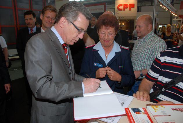 Innenminister Thomas de Maizière trägt sich in das Gästebuch des DFV ein.