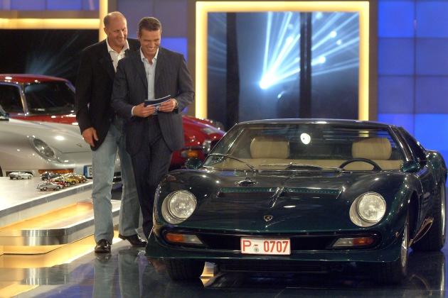 """Hans-Joachim Stuck und Moderator Jan Stecker bewundern den Lamborghini Miura – bei der Show """"Die kultigsten Autos aller Zeiten"""" am 6. Oktober 2005 bei kabel eins. © kabel eins - honorarfrei nur im Zusammenhang mit einem Sendehinweis auf das entsprechende kabel eins-Format und bei Nennung """"Bild: kabel eins""""."""