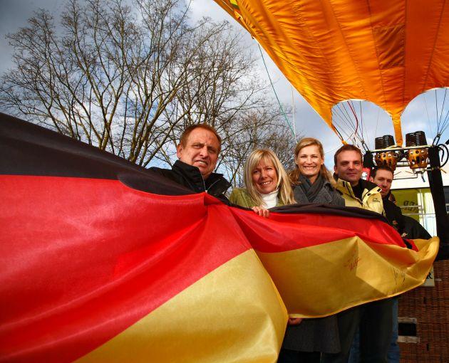 """WARSTEINER, Co-Sponsor der deutschen Olympiamannschaft und weltweiter Botschafter deutscher Bierkultur, lässt zum ersten Mal jenen Heißluftballon steigen, der die deutsche Fan-Fahne auf dem Luftweg in die Olympia-Stadt Beijing bringen wird. Mit im Ballonkorb: Jene schwarz-rot-goldene Fan-Fahne, auf der alle Fans der olympischen Spiele ihre Begeisterung und Unterstützung für ihre Athleten in Form von Unterschriften und persönlichen Worten ausdrücken können. Heike Henkel, Dreifach-Olympionikin und Hochsprung-Olympiasiegerin von 1992, unterschrieb im Rahmen des Auftakt-Presse-Events als Erste auf der Fan-Fahne.  Abgebildete Personen (von links): Herman Löser (Geschäftsführer WIM GmbH und Pilot des WARSTEINER Olympia-Ballons), Ulrike von der Groeben (RTL-Moderatorin), Heike Henkel (Hochsprung-Olympiasiegerin 1992), Thorsten Terlohr (Leiter Sponsoring/Event der Warsteiner Brauerei und Verantwortlicher der Aktion), Thomas Siebel (WARSTEINER Ballooning Team und Pilot des WARSTEINER Olympia-Ballons) Die Verwendung dieses Bildes ist für redaktionelle Zwecke honorarfrei. Abdruck bitte unter Quellenangabe: """"obs/Warsteiner Brauerei"""""""