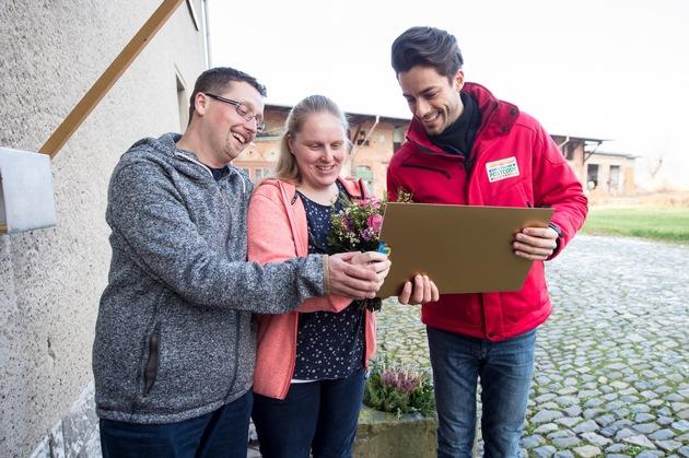 Postcode-Moderator Giuliano Lenz (rechts) überrascht Straßenpreis-Gewinnerin Beate und ihren Ehemann Christoph. Foto: Postcode Lotterie/Marco Urban