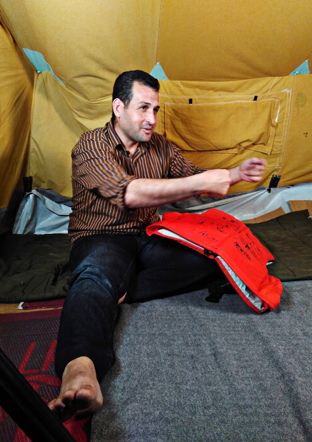 "The 29 year old vet Farooq Saadi from Qamishli in Syria conversing in his tent in the ""Oreokastro"" refugee camp in Thessaloniki, Greece. On his knee is the life jacket bearing his life story. In October 2016, as part of ""Project Life Jacket"", the life stories of nine Syrian refugees were illustrated on life jackets used for the crossing to Lesbos. Picture taken on the 7th October 2016 in Thessaloniki. (Project Life Jacket). Texte complémentaire par ots et sur www.presseportal.ch/fr/nr/100061210 / L'utilisation de cette image est pour des buts redactionnels gratuite. Publication sous indication de source: ""obs/Project Life Jacket"""