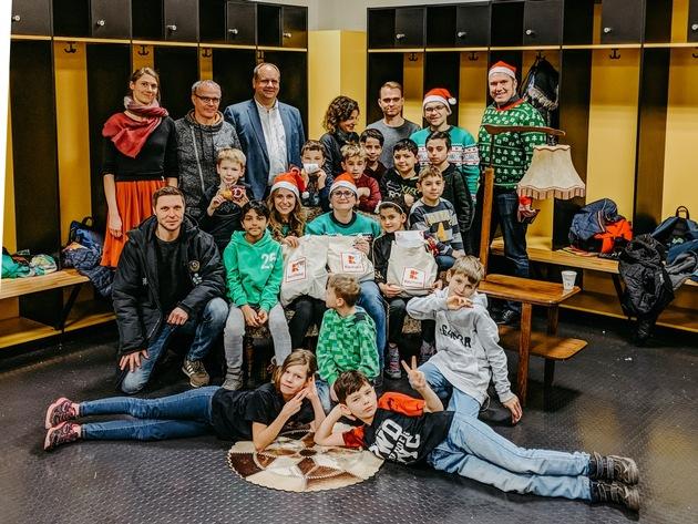 """Kinder des Projekts """"Fußball trifft Kultur"""" in Dresden freuen sich über Geschenke von Kaufland, die sie nach einer gemeinsamen Führung durchs Rudolf-Harbig-Stadion erhielten. Foto: Kaufland"""