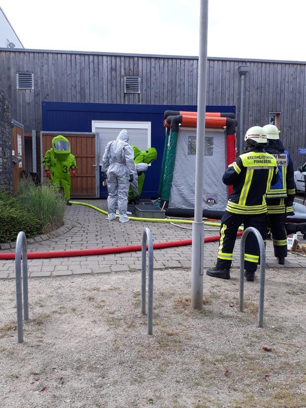 Kräfte im Chemiekalienschutzanzug verlassen das Gebäude