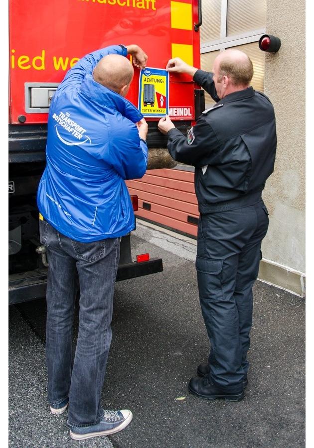 """Gunnar Becker und Guido Vogt bringen den """"Toter Winkel""""-Aufkleber an einem der Fahrzeuge an."""