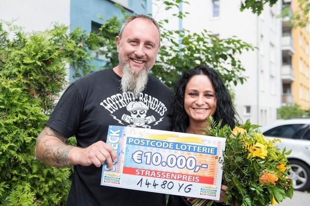 Straßenpreis-Gewinner René und seine Freundin Patricia freuen sich über den 10.000-Scheck. Foto: Postcode Lotterie/Marco Urban