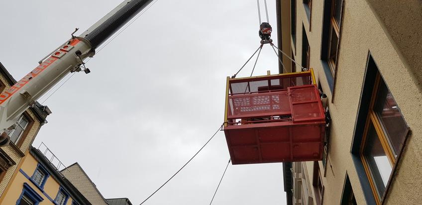 Der Personenaufnahmenkorb am Fenster im zweiten Obergeschoss. Mittels Seilen wird verhindert das der Korb sich beim Rüberheben der Patientin vom Gebäude wegdrückt.