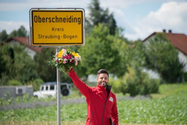 Postcode-Moderator Giuliano Lenz hat Gerd den Gewinnerscheck persönlich überreicht. Foto: Postcode Lotterie/Wolfgang Wedel