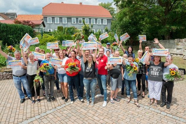 Strahlende Gewinner: Katarina Witt und Felix Uhlig überraschen insgesamt 27 Teilnehmer der Deutschen Postcode Lotterie aus Gräfenroda und Umgebung. Foto: Postcode Lotterie/Wolfgang Wedel