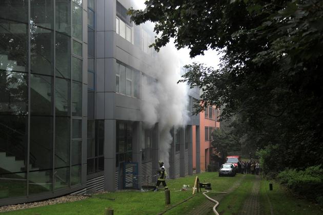Rauch dringt aus den Entlüftungsöffnungen der Tiefgarage. Hier bereits weißer Rauch, ein Hinweis darauf, dass die Löschmaßnahmen Wirkung zeigen. Foto: Mike Filzen