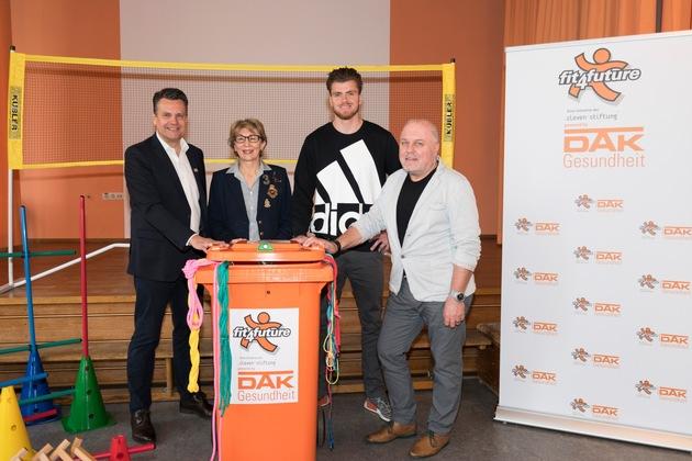 Übergaben die fit4future-Tonne (von links): Malte Heinemann (Cleven-Stiftung), Sophie Schwab (Landesvertretung DAK-Gesundheit Bayern), Rico Freimuth (Zehnkämpfer), Bernhard Ziegler (Schulleiter)