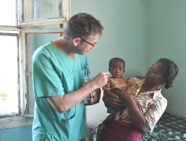 Dr. Harald Kaisers (links im Bild) mit einem madagassischem Kind und dessen Mutter.