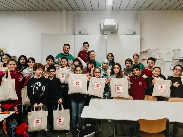 """Kinder des Projekts """"Fußball trifft Kultur"""" in Nürnberg freuen sich über Geschenke von Kaufland, die sie nach einem gemeinsamen Spielenachmittag im Klassenzimmer erhielten. Foto: Kaufland"""