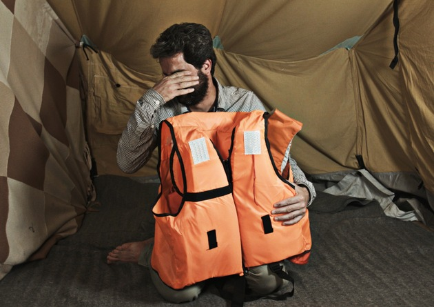 "32 year old Ismail Nerabani from Hums, Syria reacting to the life jacket bearing his life story, as he sees it for the first time. The French teacher is temporarily staying in the refugee camp ""Oreokastro"" in Thessaloniki, Greece. In October 2016, as part of ""Project Life Jacket"", the life stories of nine Syrian refugees were illustrated on life jackets used for the crossing to Lesbos. Picture taken on the 7th October 2016 in Thessaloniki. (Project Life Jacket). Texte complémentaire par ots et sur www.presseportal.ch/fr/nr/100061210 / L'utilisation de cette image est pour des buts redactionnels gratuite. Publication sous indication de source: ""obs/Project Life Jacket"""
