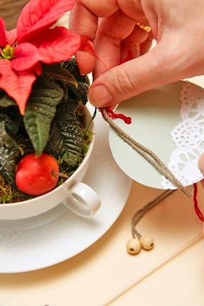 Zum Schluss die Ornamente mit Garn am Henkel der Gefäße befestigen. An dem Garn befestigte Perlen verleihen den dekorativen Anhängern das gewisse Etwas.