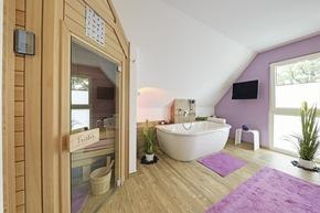 Das Badezimmer wartet mit einer edlen Wanne und einer  Sauna auf. Extravagant: die farblich zur Wand passenden Teppiche und der Fernseher.