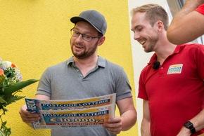 """Ionel (l., hier mit Postcode-Moderator Felix Uhlig) kann es kaum glauben und findet den Gewinn bei der Postcode Lotterie """"mega""""! Foto: Postcode Lotterie/Wolfgang Wedel"""