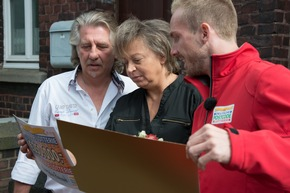 Christa aus Essen wurde von Postcode-Moderator Felix Uhlig (rechts) persönlich mit dem Gewinnerscheck überrascht. Ehemann Jörg blickt gebannt. Foto: Postcode Lotterie/Wolfgang Wedel