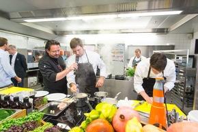 Starkoch Kolja Kleeberg mit dem Gewinnerteam in der Küche.