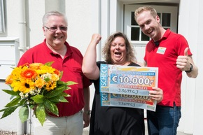So konnte er seiner Ehefrau noch einen Traum erfüllen und überreichte ihr einen orangenen Briefumschlag mit 750 Euro. Foto: Postcode Lotterie/Wolfgang Wedel