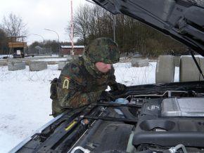 Bootsmannsanwärter Maat Robert Reil untersucht ein Fahrzeug am Übungs-Checkpoint. Er schaut in den Motor eines Geländewagens. Foto: Detlef Struckhof, Deutsche Marine