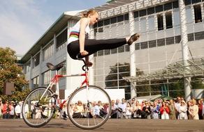 Lisa Hattemer, Weltmeisterin im Kunstradfahren, zeigt ihr Können vor zahlreichen MSD Mitarbeitern vor der Firmenzentrale in Haar.