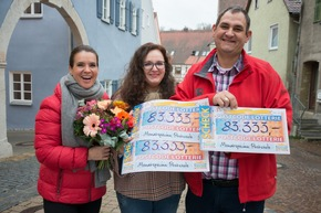 """Der strahlende Monatsgewinner Ciprian (r.) mit Ehefrau Ana-Maria (m.) und Katarina Witt. Fotocredit: """"Postcode Lotterie/Wolfgang Wedel"""""""