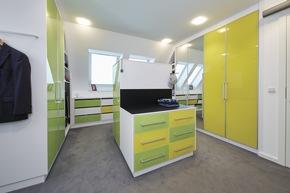 In der Ankleide haben die Schränke und Schubladen eine gelbe oder grüne Front: gelb sind ihre, grün seine Bereiche.