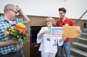 300.000 Euro? Gaby kann es kaum glauben und schaut zu ihrem Ehemann Andreas (links). Postcode-Moderator Giuliano Lenz beobachtet. Foto: Postcode Lotterie/Marco Urban