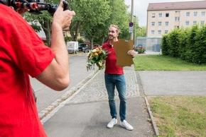 Postcode-Moderator Felix Uhlig auf dem Weg zum Gewinner aus Fürth. Foto: Postcode Lotterie/Wolfgang Wedel