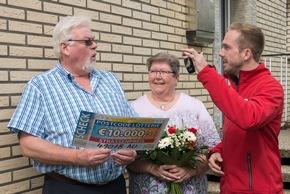 Postcode-Moderator Felix Uhlig (rechts) überreicht Klaus und seiner Ehefrau Monika die Schlüssel für den neuen BMW 1er. Foto: Postcode Lotterie/Wolfgang Wedel