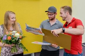 Ionel (m.) und seine Lebensgefährtin Viktorija (l.) mit Postcode-Moderator Felix Uhlig (r.) und den Schecks über 20.000 Euro! Foto: Postcode Lotterie/Wolfgang Wedel