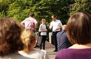 Christoph Habereder, Direktor Gesundheitspolitik und Kommunikation bei MSD, und Wolfgang Stenger, Procurement Lead Germany bei MSD, begrüßen Lisa Hattemer, Weltmeisterin im Kunstradfahren.