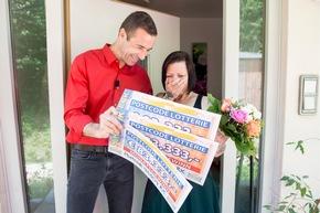 Kai Pflaume ist persönlich nach Kelheim gekommen, um Doreen die Gewinnerschecks zu überreichen. Foto: Postcode Lotterie/Marco Urban