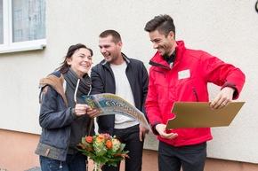 "Eine schönere Überraschung konnte Postcode-Moderator Giuliano Lenz (rechts) dem jungen Paar nicht bereiten. Foto: ""Postcode Lotterie/Marco Urban"
