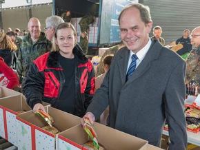 Teamarbeit: Präsident Georg Stuke und Katharina befüllen ein Paket mit Tütensuppe (Quelle: PIZ Personal/Andreas Metka)