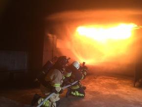 Flash-Over Simulation im Brandübungshaus. Feuerwehrleute bei der Brandbekämpfung