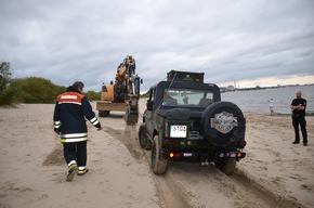Bagger zieht den Geländewagen über den Strand